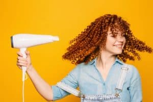 Curly red-haired woman using hair dryer on yellow background. Making perfect curls